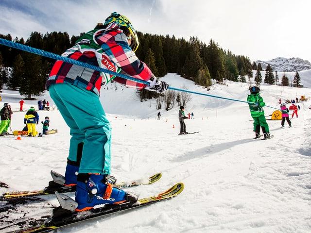 Ein Seil-Skilift, an dem sich mehrere Kinder festhalten.