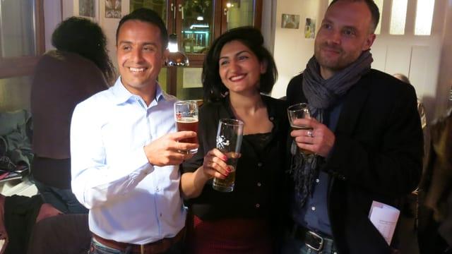 Sibel Arslan posiert mit zwei Parteifreunden f¨r den Fotografen, alle haben ein Bier in der Hand.