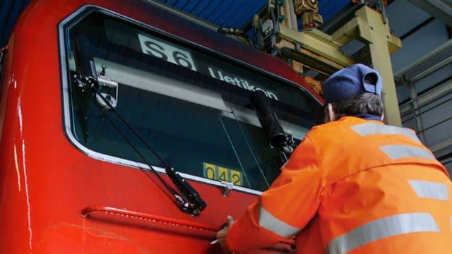 Ein SBB-Arbeiter putzt die Frontscheibe einer S-Bahn-Lokomotive.