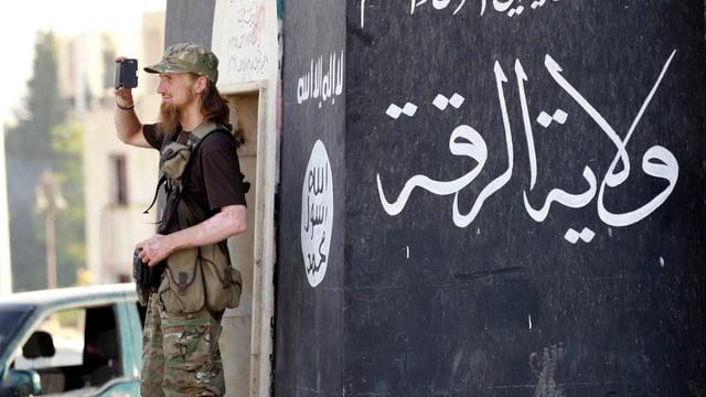 Aufnahme aus Rakka: Bewaffneter Mann mit rot-blondem Bart vor einer IS-Flagge mit Filmkamera in der Hand.