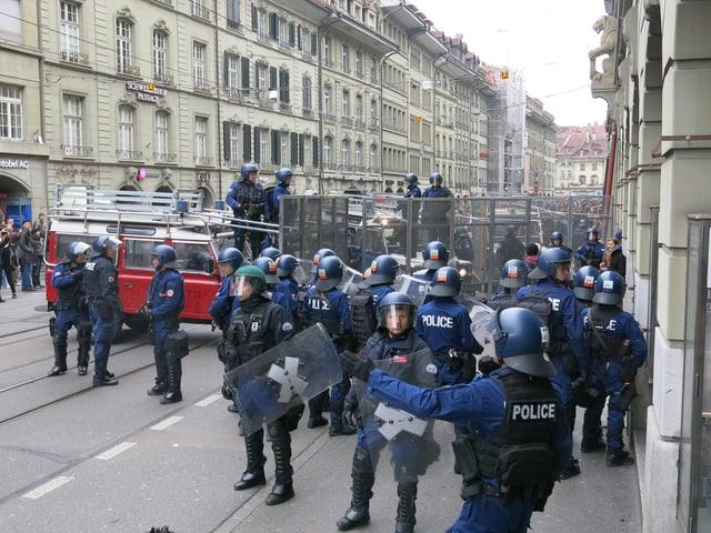 Polizisten mit Absperrgittern.