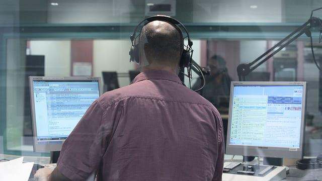 Blick durch die Scheibe in die Sprecherkabine des Radiostudios, Moderator von hinten an zwei Bildschirmen, im Hintergrund durch eine weitere Scheibe ein Techniker zu sehen.