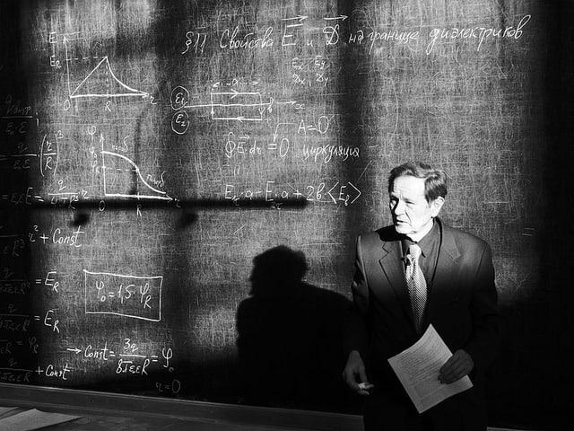 Ein Professor vor einer Wandtafel. Darauf sind Formeln.