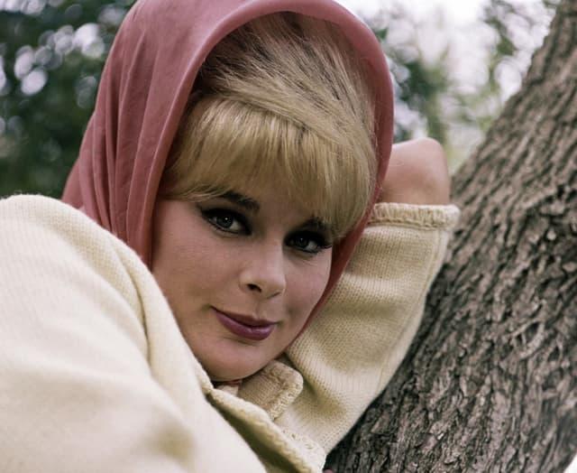 Elke Sommer lehnt sich an Baumstamm. Sie trägt einen beigen Mantel und ein rosa Kopftuch.
