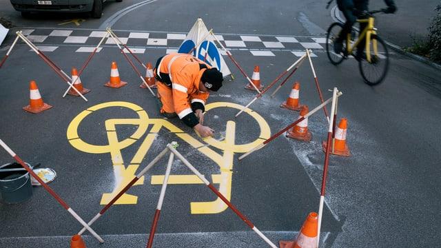 Ein Arbeiter bringt eine grosse Velomarkierung auf einer Strasse an.