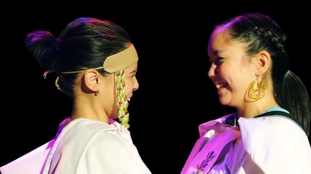 Zwei Frauen in traditioneller Kleidung lachen sich an.