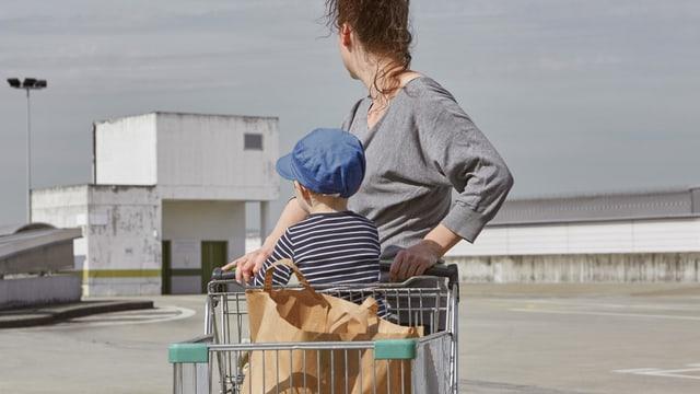 Eine Frau schiebt einen Einkaufswagen, in dem ein Kind sitzt, auf dem Dachgeschoss eines Parkhauses. (keystone)