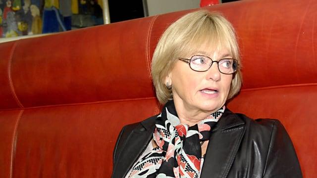 Pia Kjærsgaard, auf einem roten Polstersofa sitzend.