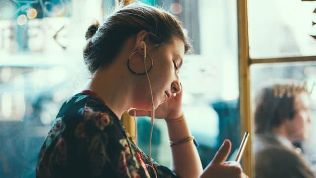 Frau mit Kopfhörern im Ohr sitzt im Bus.
