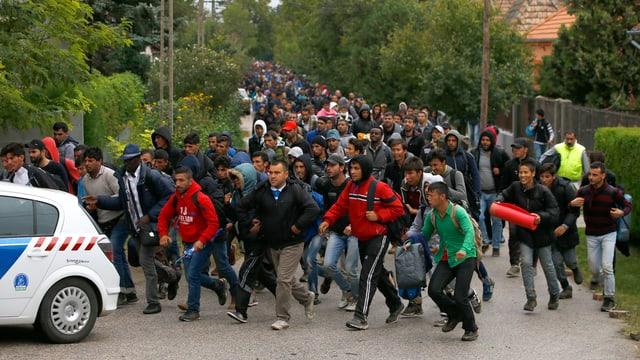 Flüchtlinge auf einer Strasse hinter einem Polizeiauto.
