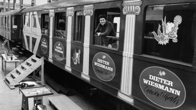 Schwarz-Weiss-Fotografie mit einem Mann der aus dem Fenster eines Zugwaggons schaut.
