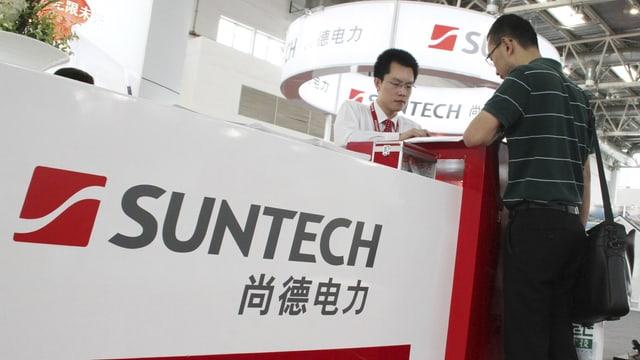 Ein Angesteller informiert einen Interessenten über die Suntech-Produkte an einer Messe in Peking. (reuters)