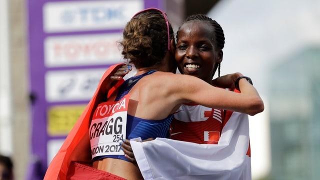 Rose Chelimo und die drittklassierte Amy Cragg liegen sich nach dem Zieleinlauf in den Armen.