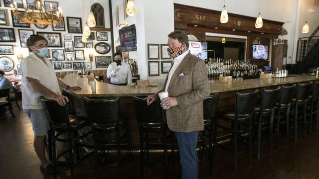 Zwei Männer mit Gesichtsmasken stehen an einer Bar