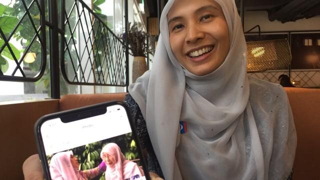 Nurul Izzah Anwar hält lächelnd ihr Smartphone in die Kamera