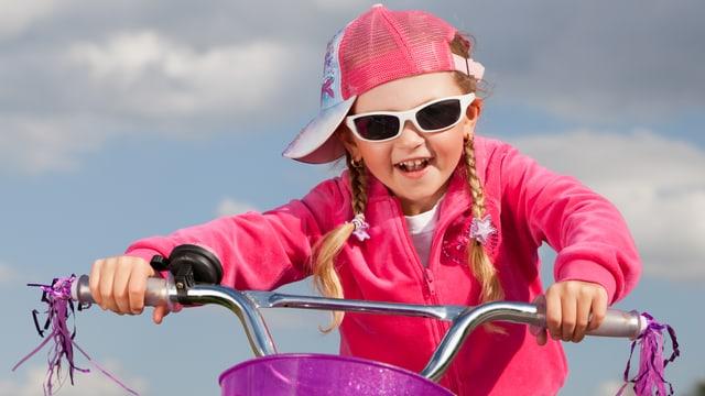 Kleines Mädchen mit Basecap und Sonnenbrille sitzt auf Retro-Fahrrad