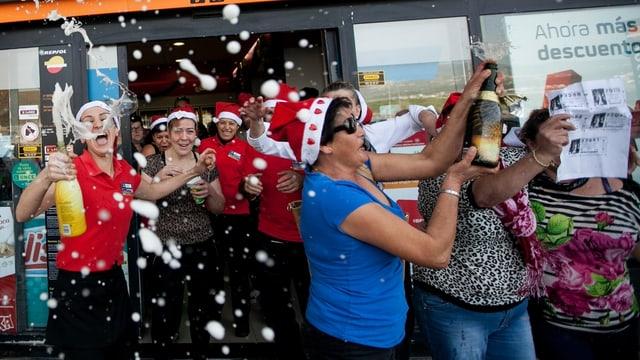 Frauen mit Losen, Nikolaushüten und Champagnerflaschen feiern ausgelassen.