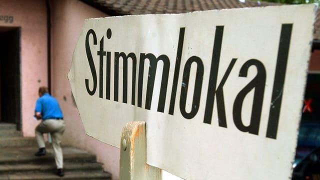 """Ein Schild in Pfeilform, darauf steht schwarz """"Stimmlokal"""""""