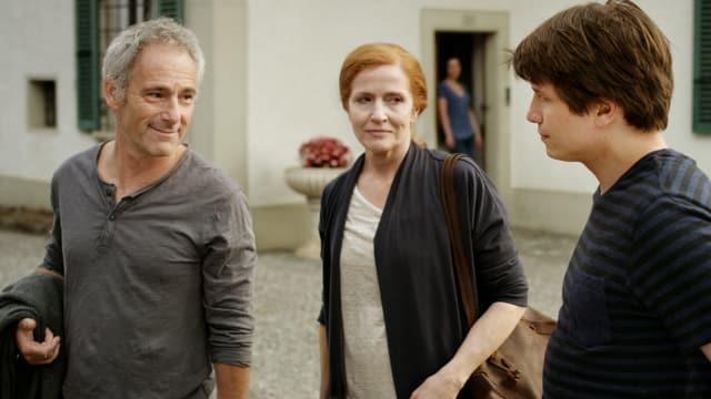 Ein Mann, eine Frau und ein Junge stehen draussen vor einem Gebäude.