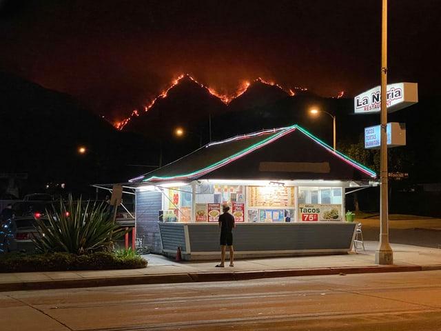 Mann bei Drive-In, im Hintergrund brennende Wälder