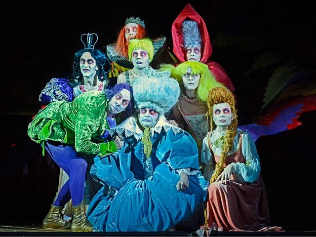 Eine Gruppe von Läuten mit bunten Kostümen, gleben, weissen und violetten Haaren.