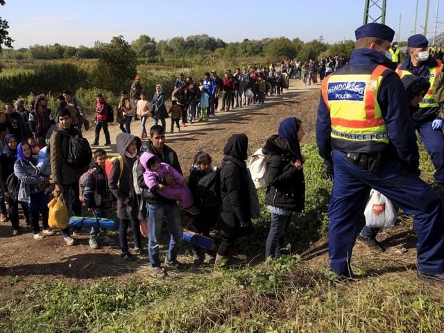Menschen stehen auf einem Feldweg Schlange