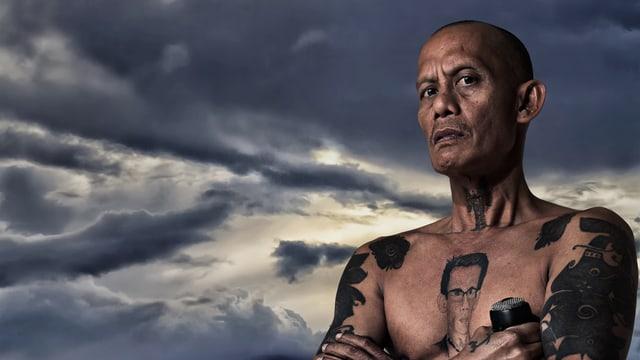 Ein tätowierter Mann mit nacktem Oberkörper. Im Hintergrund ein dunkler Himmel mit Wolken.