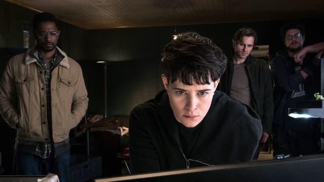 Im Vordergrund: Eine Frau mit kurzen Haaren und Nasenpiercing schaut konzentriert in einen Bildschirm, ihr Gesicht wird von Licht des Computers angeleuchtet. Im Hintergrund stehen drei Männer und schauen ihr zu.