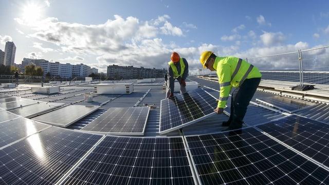 Zwei Männer installieren Solarpanels auf einem Hausdach.