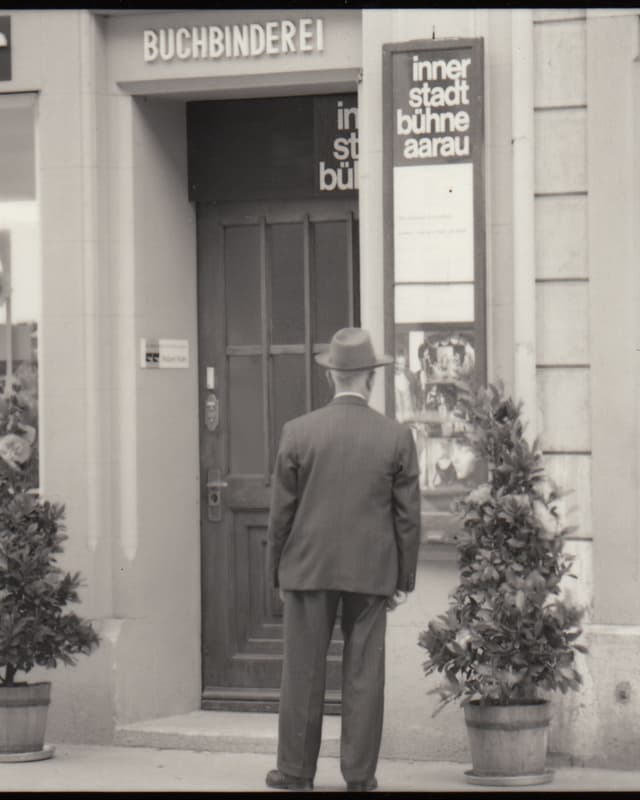 Schwarzweiss Foto: Mann steht vor Eingang