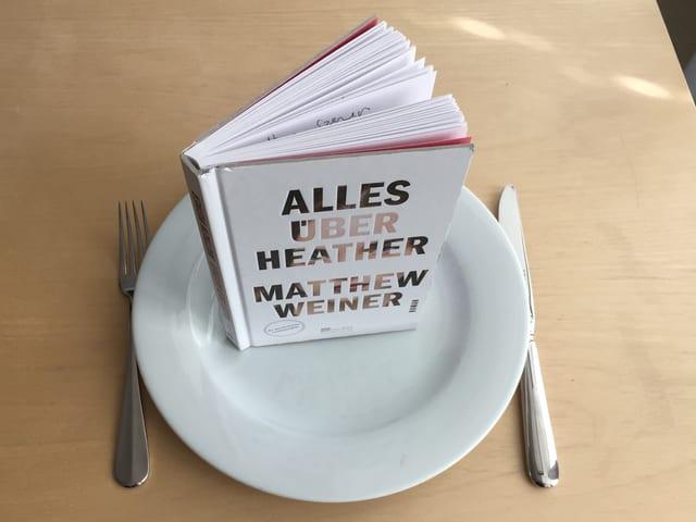 «Alles über Heather» von Matthew Weiner steht auf einem weissen Teller. Meser und Gabel daneben.