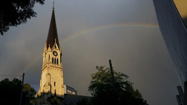 Kirchturm mit Regenbogen im Hintergrund
