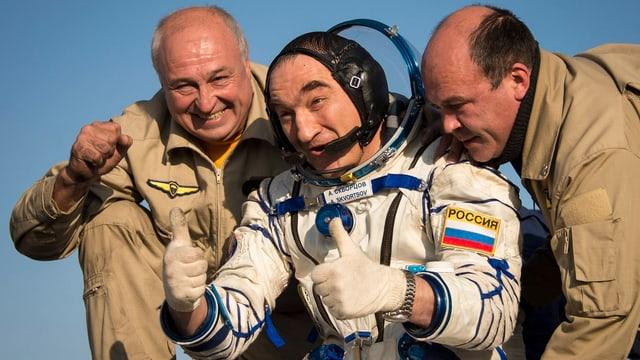 Eine Person in einem Raumfahrt-Anzug mit erhobenen Daumen.