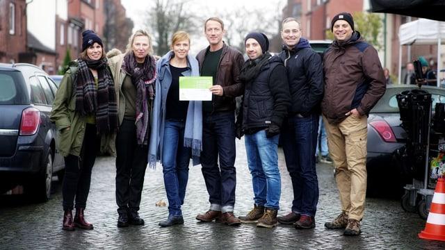 Sieben Personen stehen nebeneinander und schauen in die Kamera. Einer hält einen grünen Zettel.