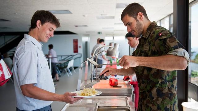 Ein Soldat schenkt einem anderen Teiwaren aus.