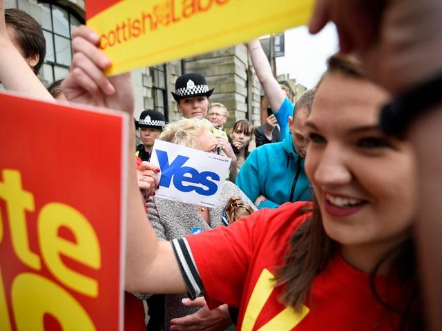 Eine junge Demonstrantin hält ihr Nein-Plakat in die Höhe, hinter ihr steht eine ältere Frau, die klar für die Abspaltung Schottlands ist. (reu)