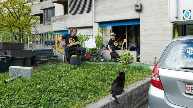 Zwei Männer sitzen draussen – mit Katze und Hund.