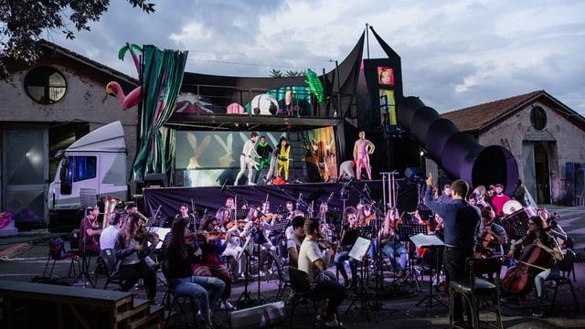 Ein Orchester vor einem Lastwagen mit einer Bühne