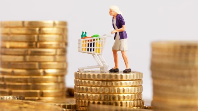 Frau mit Einkaufswagen, auf einem Berg von Münzen.