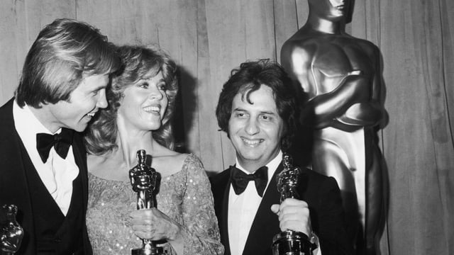 Zwei Männer und eine Frau halten die Oscar-Statue
