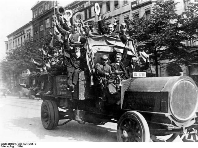 Jubelnde deutsche Reservisten in Berlin auf einem Auto.