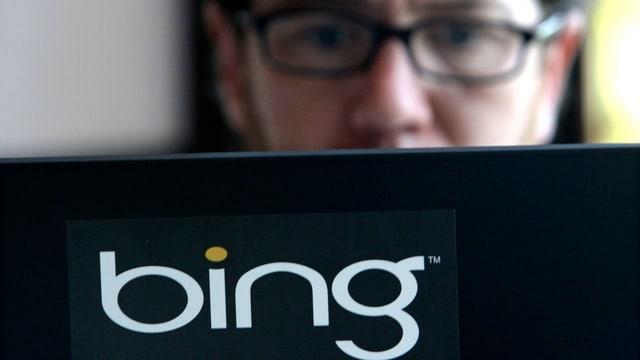 Laptop mit Bing-Logo. Person mit Brille schaut in den Bildschirm
