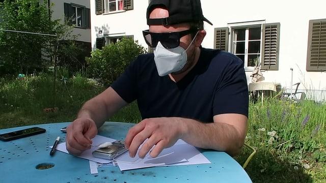 Mann mit Maske arbeitet am Tisch