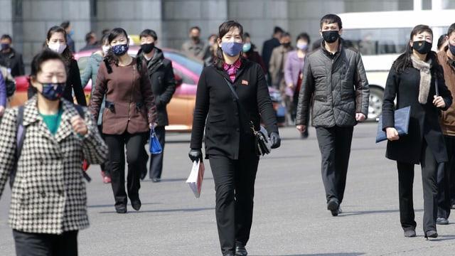 Nordkoreanerinnen und Nordkoreaner tragen auf der Strasse Masken