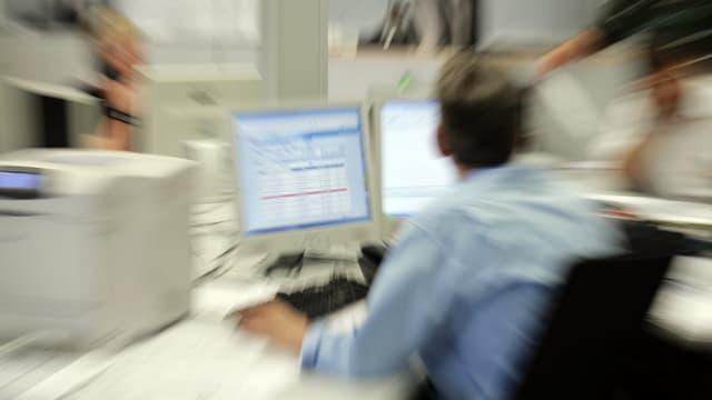 Ein Büroangestellter von hinten vor zwei Bildschirmen.