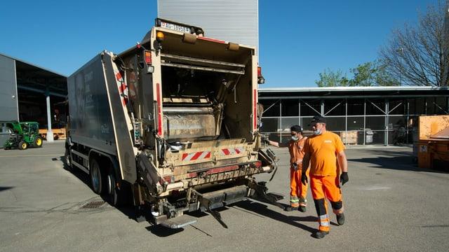 Der Arbeitstag zweier Müllmänner beginnt. Einer steht schon auf der Plattform der Kehrichtabfuhr und der andere springt drauf