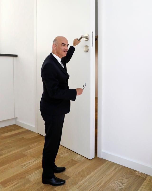 Alain Berset öffnet eine übergrosse Tür