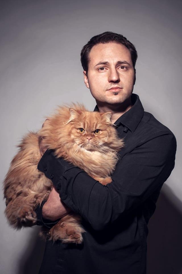 Portrait von Alain Bieber, der eine Katze auf dem Arm hält.