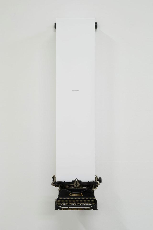 Eine altmodische Schreibmaschine hängt an einem langen Papierstreifen, der in der Maschine eingespannt ist.