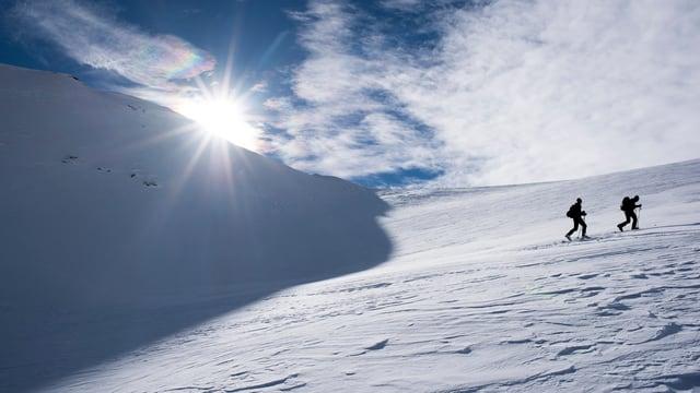 Zwei Skitourengeher im Aufstieg auf einen Berg.